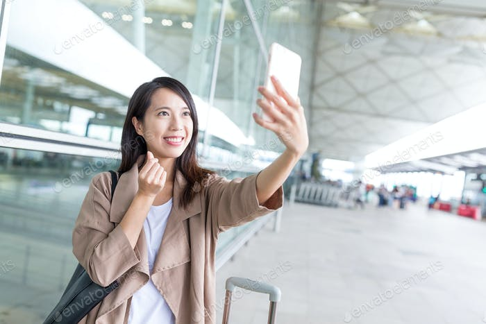 Woman taking selfie and posing korean haert gesture