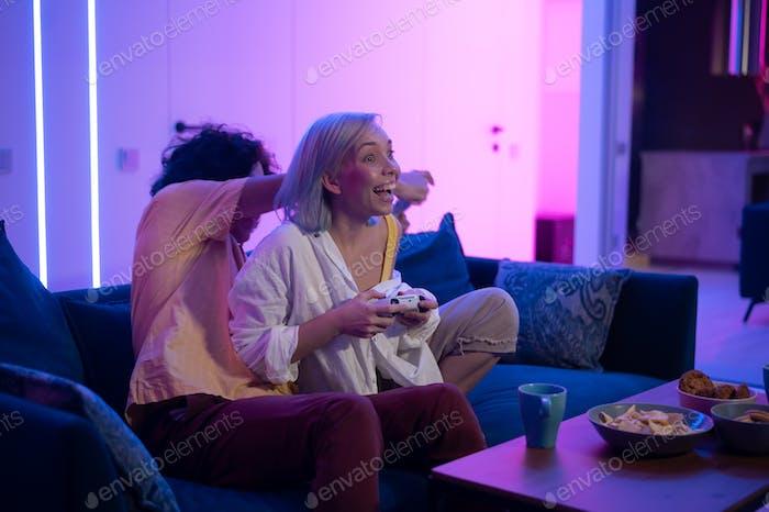 Feliz pareja joven jugando y ganando una actividad divertida juego sentado en casa en un sofá