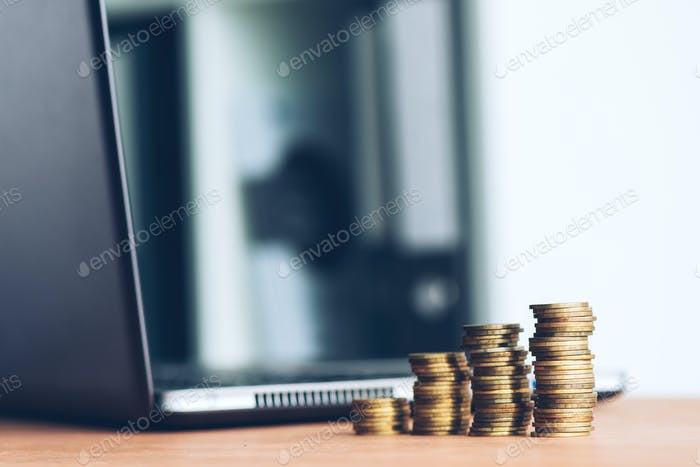 Stacked money coins and laptop computer