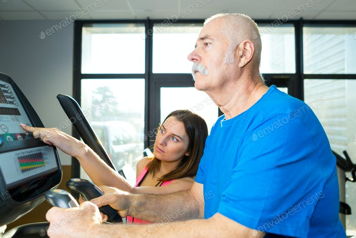 senior man using electronic exercise machine under supervision