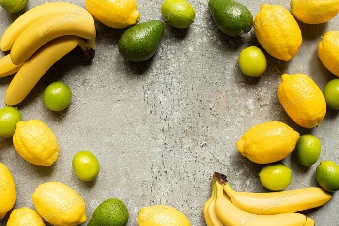 Top View of Colorful Bananas, Avocado, Limes And Lemons on Grey Concrete Surface With Copy Space