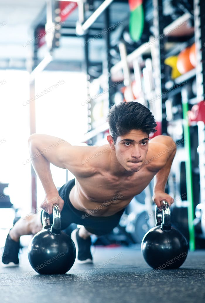 junge fit hispanic Mann in Fitness-Studio tun Push-ups auf Kettlebells