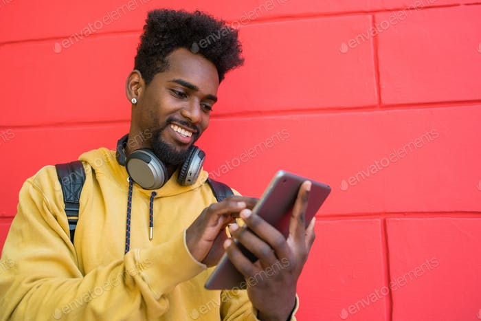 Afro man using his digital tablet with earphones.