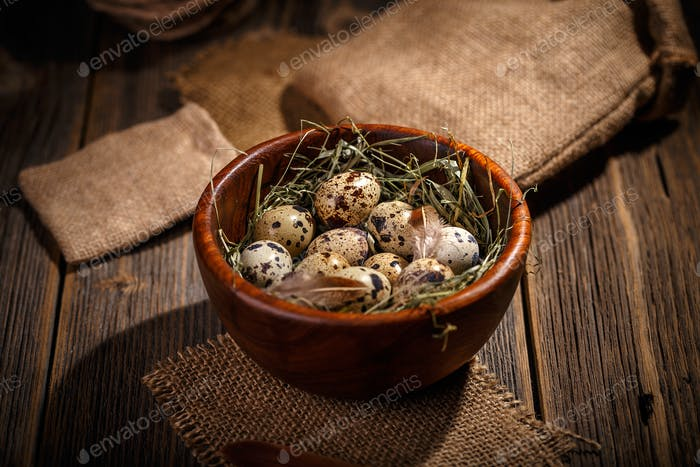 Quail eggs in wooden bowl
