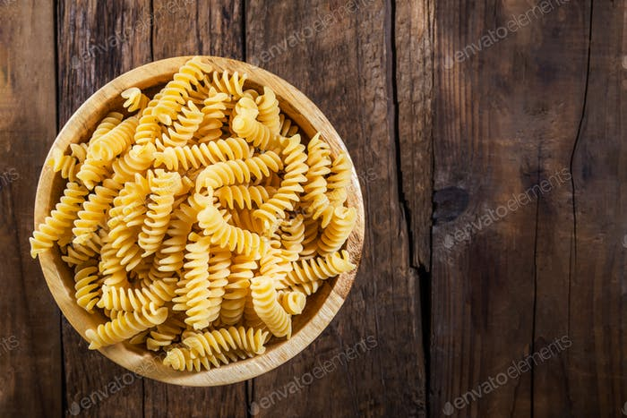 Raw Pasta Fusilli in Wooden Bowl