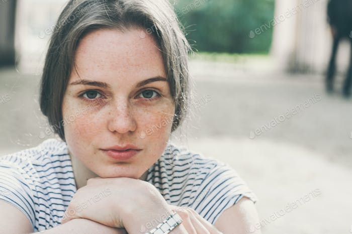 Beautiful woman face portrait freckles is sitting on the ground. Street city fashion nature.