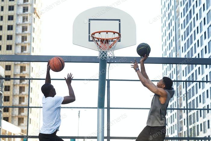 Парни, подгоняя гол в баскетболе