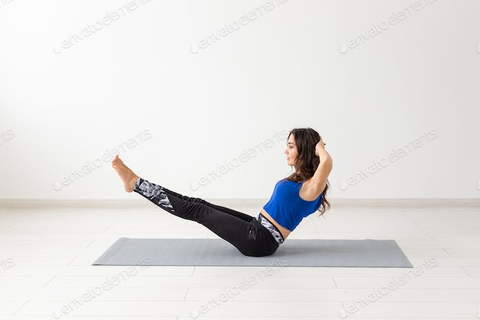 Sport, people concept - young woman swinging press by statics exercises