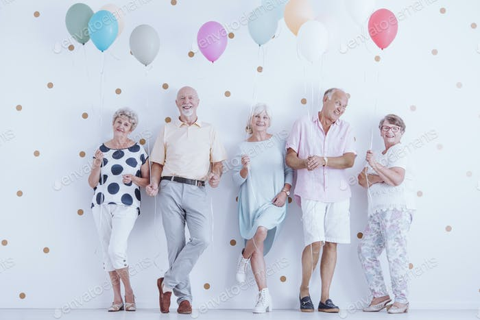 Happy pensioners holding balloons