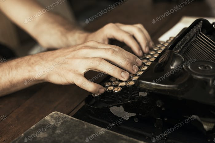 Young man's hands typing on an antique vintage typewriter