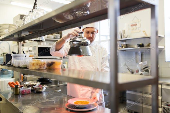 männlicher Koch Heizung Essen mit Lampe in der Küche