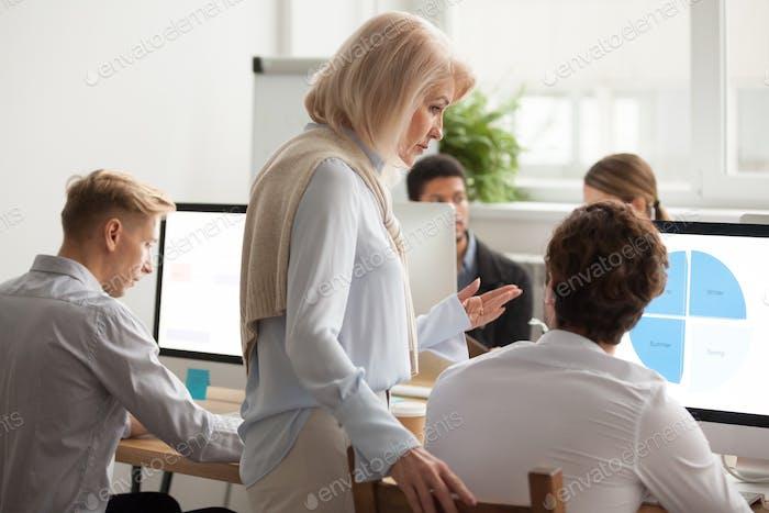 Mentora ejecutiva superior supervisando Trabajo Ordenador de la joven pasante