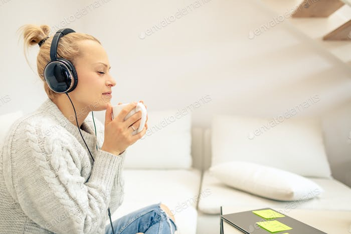 Young woman listening to music and enjoying cup of coffee