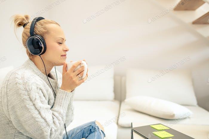 Junge Frau Musik hören und eine Tasse Kaffee genießen