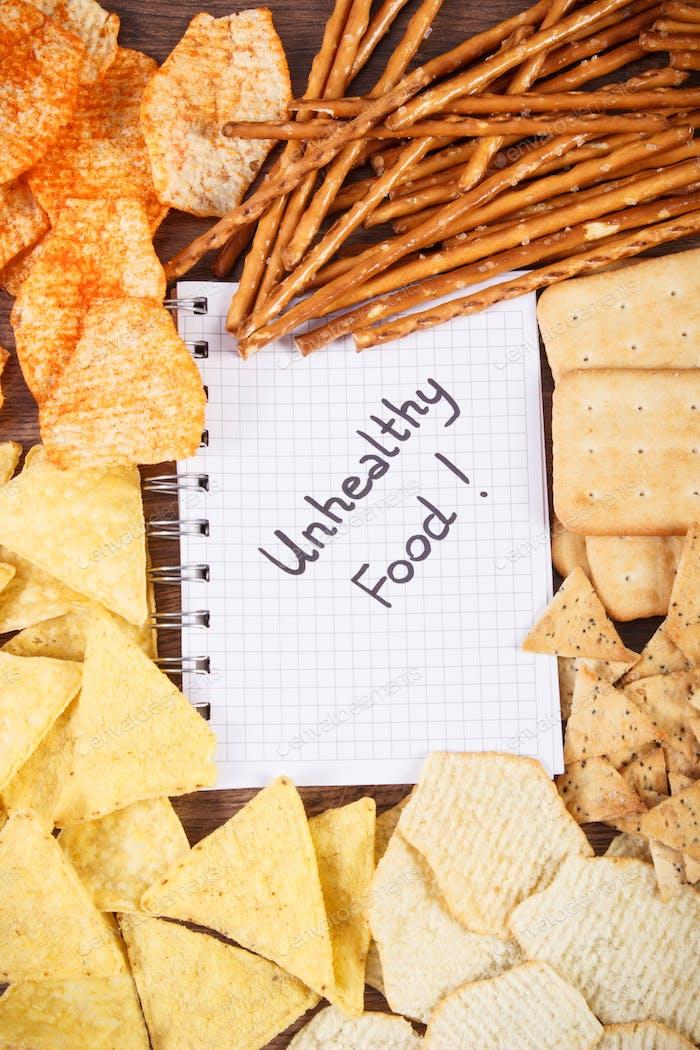 Надпись нездоровой пищи в ноутбуке и куче чипсов и печенья