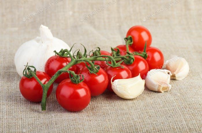 Cherry tomatoes and garlic over  jute fabric