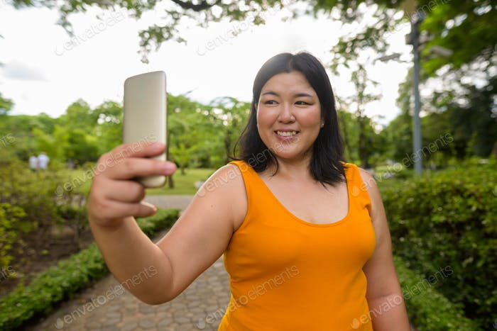 Beautiful overweight Asian woman taking selfie in park
