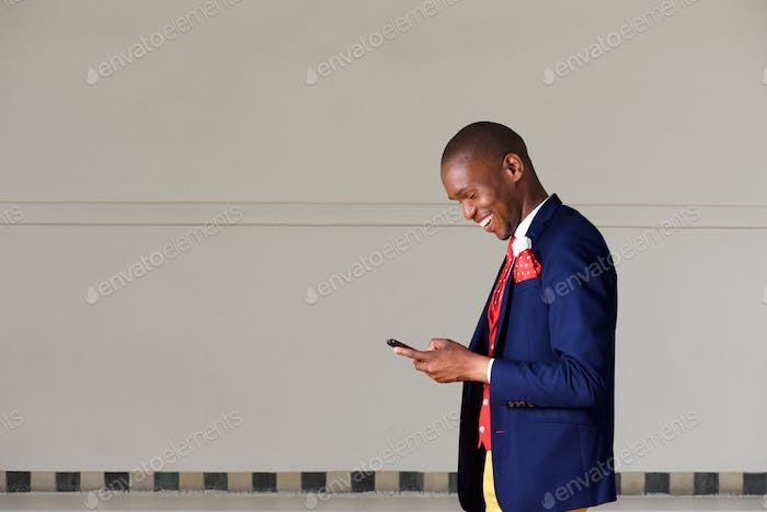 young businessman using mobile phone and walking outdoors