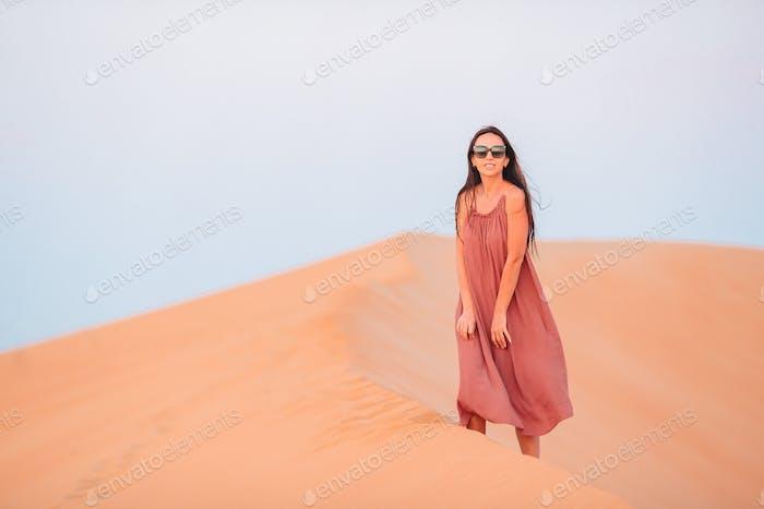 Girl among dunes in desert in United Arab Emirates