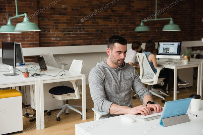 Male executive using digital tablet at desk