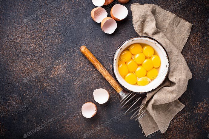 Bowl with eggs yolks and whisk