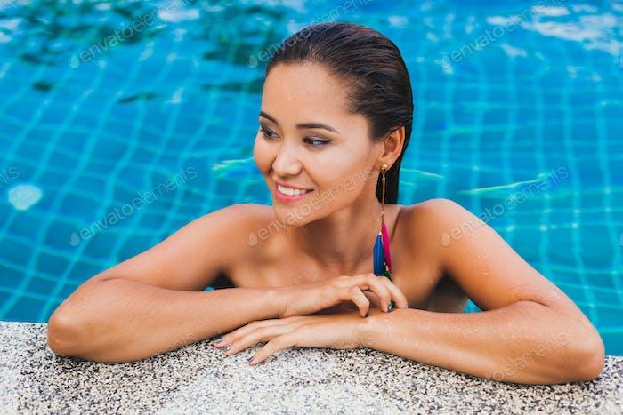 portrait of beautiful asian woman in black swimsuit bathing luxury spa swimming pool