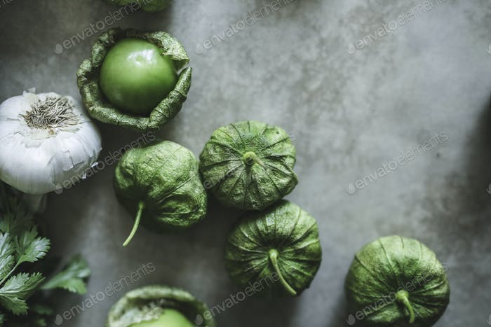 Garlic and green tomatillos on a gray table