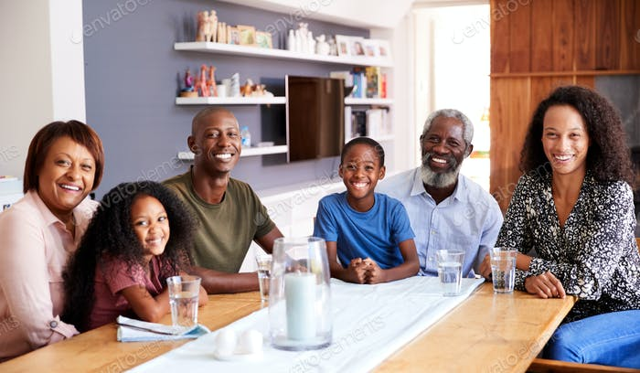 Portrait Of Multi-Generation Family Sitting Around Table At Home Enjoying Meal Together