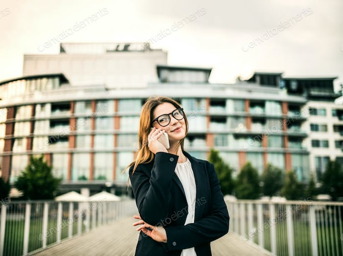 A young businesswoman with smartphone standing on the bridge in a city.
