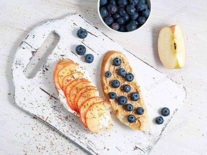 Healthy breakfast with sweet sandwiches - ricotta, blueberries, apple slices, peanut butter