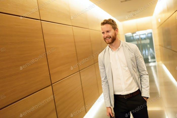 Happy businessman walking on corridor