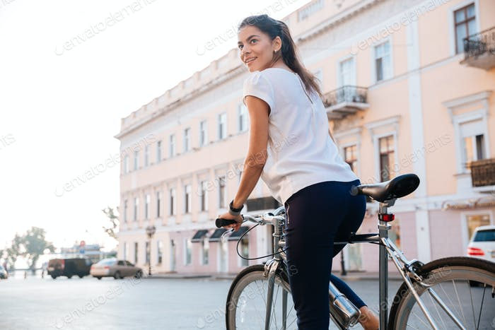 Portrait of a charming woman riding on bicycle