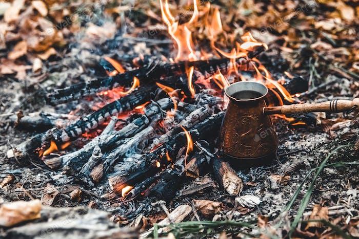 Kaffee auf dem Scheiterhaufen. Machen Sie Kaffee oder Tee auf dem Feuer der Natur. Verbranntes Feuer. Ein Ort für Feuer