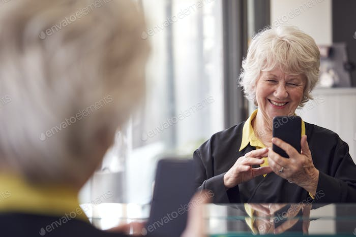 Senior Woman Waiting To Have Hair Cut In Hairdressing Salon Looking At Mobile Phone