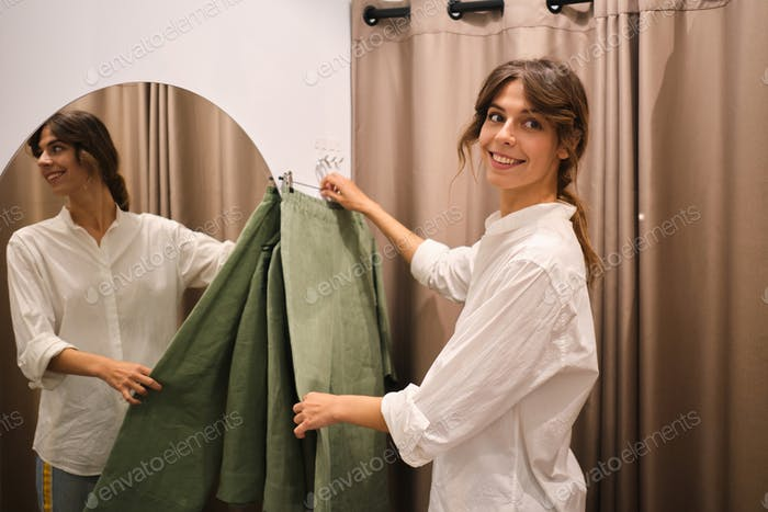 Attractive fashion consultant happily putting clothes in dressing room for customer in store