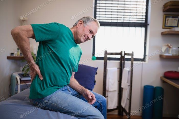 Side view of male patient suffering from back ache while sitting on bed