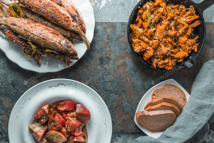 Fried chanterelles, fish on a plate, tomatoes and bread free space