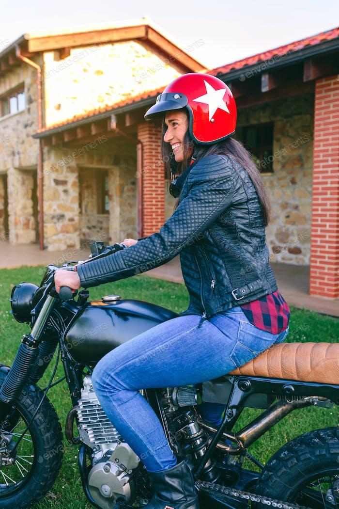 Woman with helmet riding custom motorbike