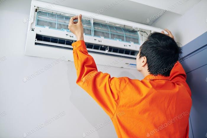 Technician installing conditioner
