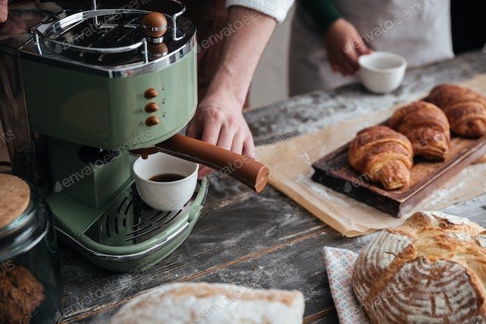 Abgeschnittenes Bild von jungen Bäckern, die bei Bäckerei Kaffee trinken.