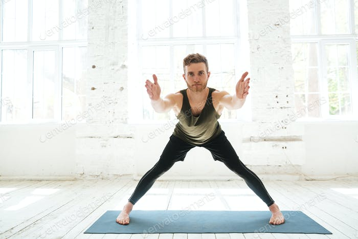 Concentrated young man parctising yoga pose on a fitness mat