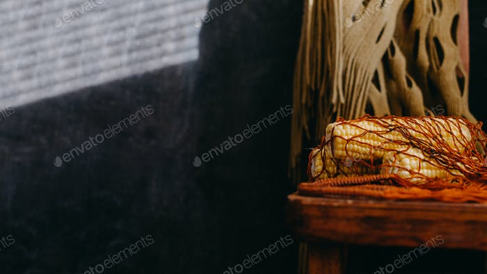 Slow food, natural vegan food concept. Rustic Still life with corn in mesh net bag on wooden chair