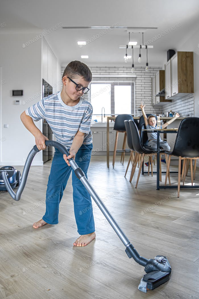 Little boy vacuums the floor of the house.