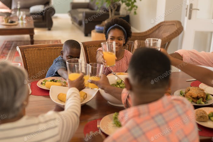 Brother and sister toasting glasses of orange juice with their family at the dinning table