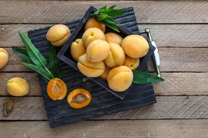 Delicious ripe apricots in a wooden box on the table. copyspace