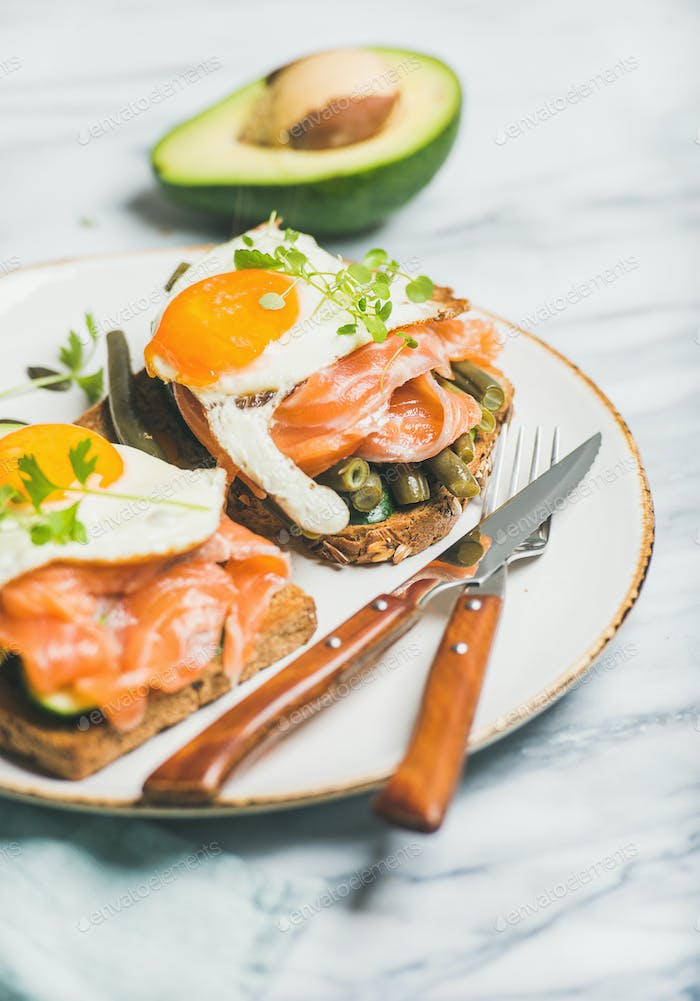 Salmon, avocado, fried egg, sauted green beans and sprouts sandwiches
