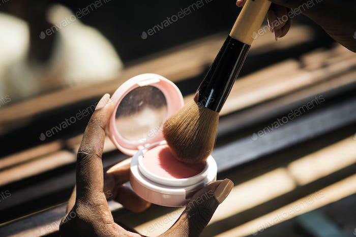 Closeup of woman using blush on
