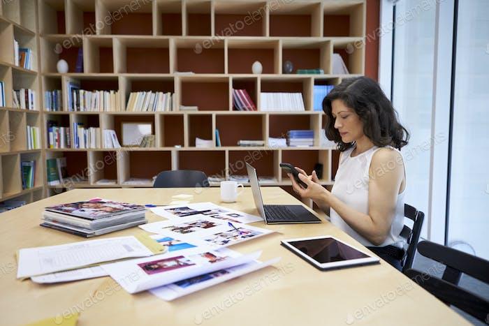 Frau im Kreativ-Media-Büro mit Smartphone an ihrem Schreibtisch