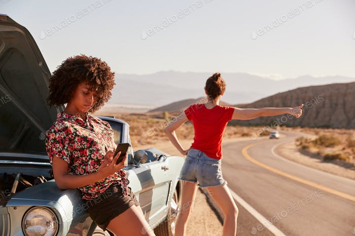 Two female friends by their broken down car at the roadside