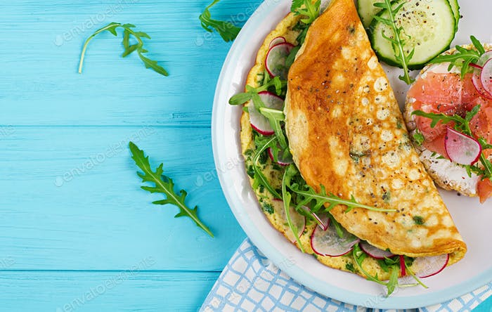 Breakfast. Omelette with radish, green arugula and sandwich with salmon